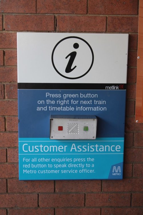 Sticker indicating the red button on the PRIDE box can be used for customer assistance, not just emergencies