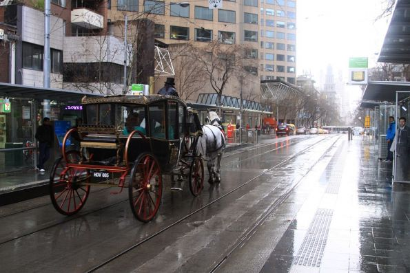 Horse drawn tram? Not quite, as a horse and carriage goes down the tram tracks in Collins Street