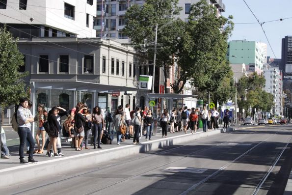 Passengers waiting at the Lincoln Square tram stop on Swanston Street