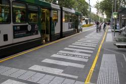 Cyclists keep clear of a stopped tram at the new Swanston Street stop