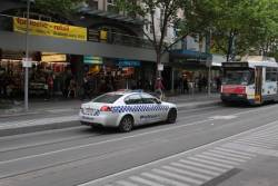 Police car heading northbound through the tram stop at Swanston and Collins Streets