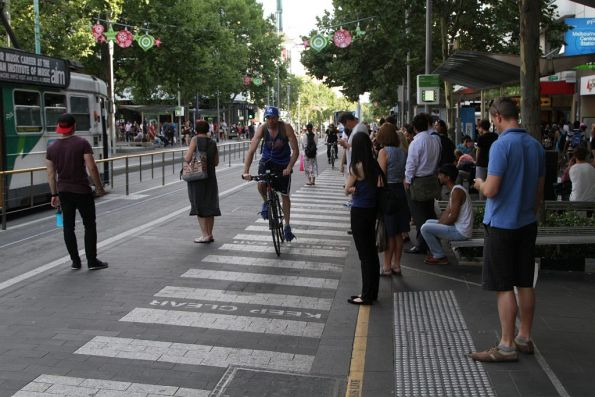 Cyclists at the Swanston Street tram stop navigate a pack of passengers blocking the bike lane