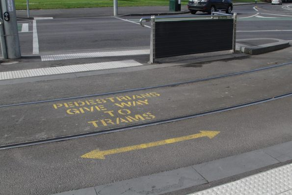 'Pedestrians give way to trams' notice between the tracks at Domain Interchange