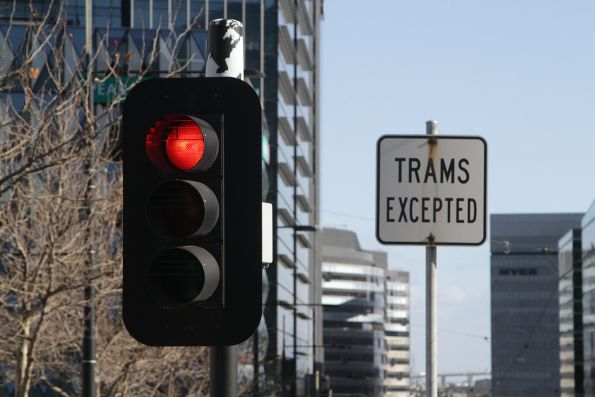 'Trams Excepted' sign next to a set of traffic lights serving a pedestrian crossing