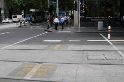 'Pedestrians give way to trams' signage on the concrete at the Collins and William Street tram stop