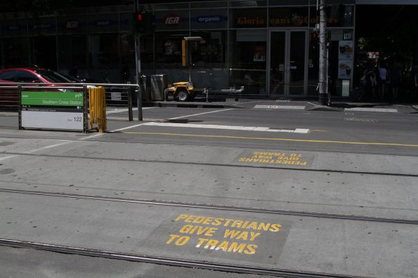 'Pedestrians give way to trams' signage on the concrete at the Spencer and Collins Street tram stop