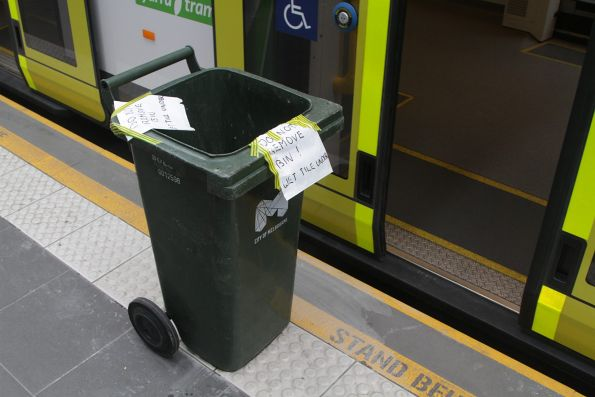 Rubbish bin covers newly repaired tactile paving at a platform stop