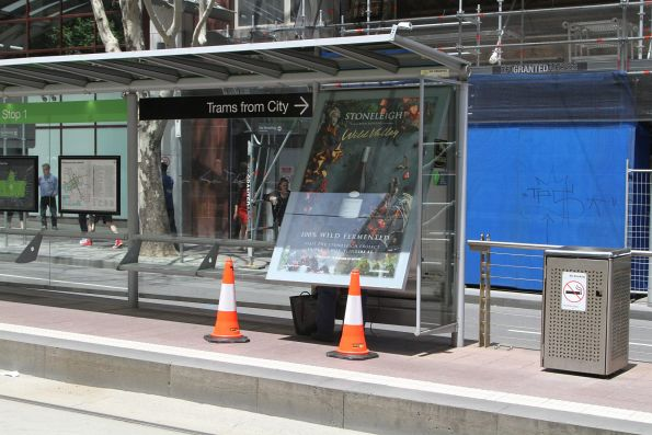 Repairing a defective advertising sign at a tram stop