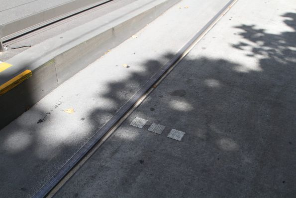 Three squares indicate the stopping point for non-E class trams at a platform stop