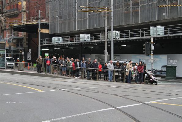 Crowd of passengers waiting for the traffic lights at the Bourke and Spencer Street tram stop