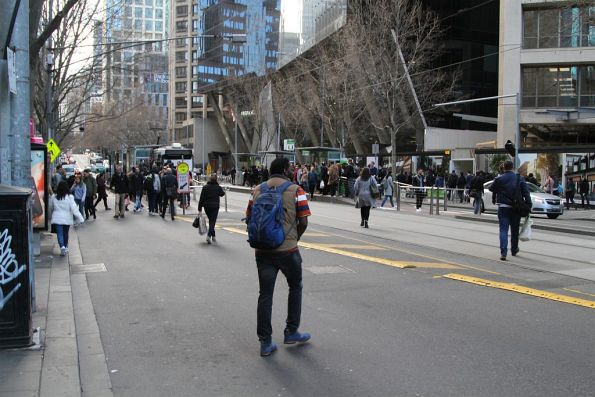 Pedestrians all over the road, bound for the poorly located eastbound tram stop at Collins and Spencer Street