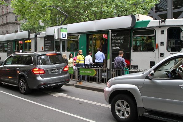 Passengers board a route 58 tram at a 'safety zone' stop at William and Bourke Street