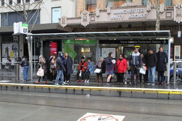 Waiting for a tram in the rain at Collins and Swanston Street