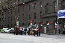 Passengers wait to exit the safety zone tram stop at William and Bourke Street