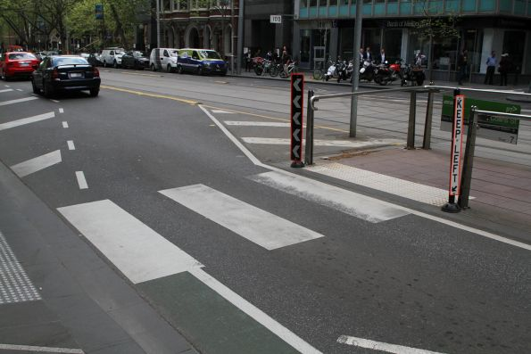'KEEP LEFT' signage beside the tram stop fence at 101 Collins Street