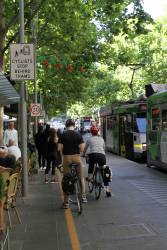 Cyclists wait behind a stopped tram on Swanston Street
