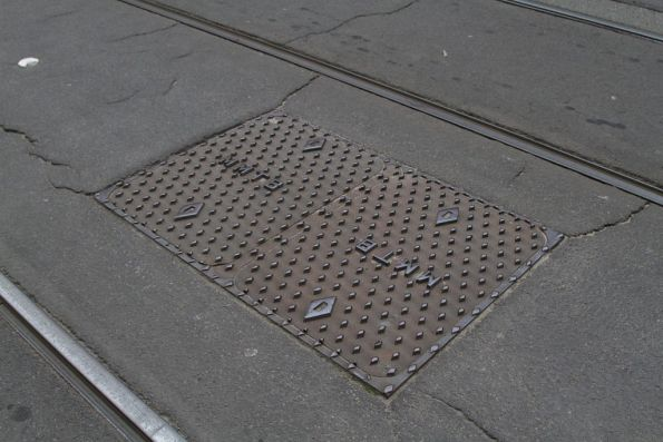 'MMTB' branded manhole covers between the tracks on La Trobe Street