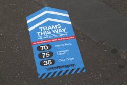 'Trams this way' notices on the footpath of Spencer Street