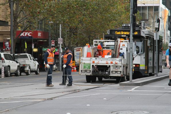 Yarra Trams staff clear gunk out of the points at La Trobe and Swanston Street with a pressure cleaner