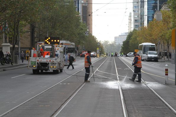 Yarra Trams staff clear gunk out of the crossover at La Trobe and Swanston Street with a pressure cleaner