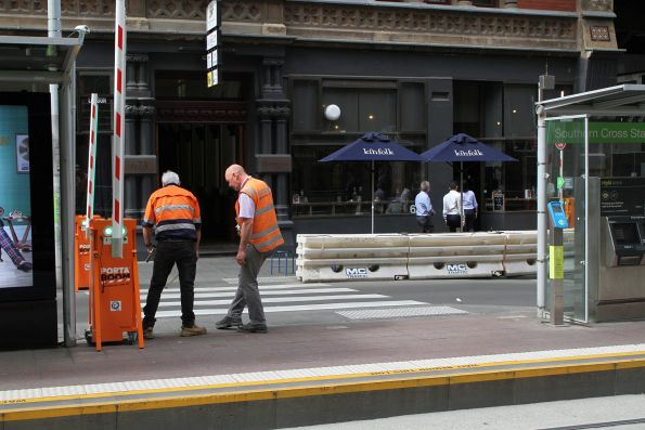 Yarra Trams staff inspect the mid block exit at the Bourke and Spencer Street tram stop