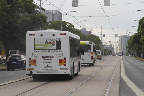 Three empty buses head down Flemington Road, so they can head back to Airport West