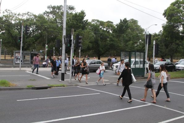 Route 59 passengers walk from the tram stop to replacement buses on Flemington Road