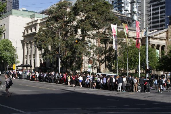 Mob of RMIT University graduates prepare to flood the next westbound tram on La Trobe Street