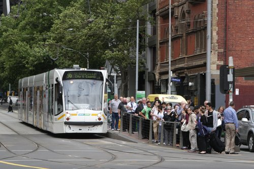 Tram load of passengers depart a route 96 service at the corner of Bourke and Spencer Streets