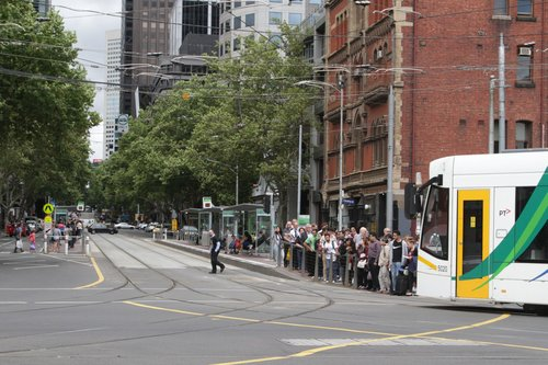 Route 96 tram clears the corner of Bourke and Spencer Streets, but departing passengers are still waiting