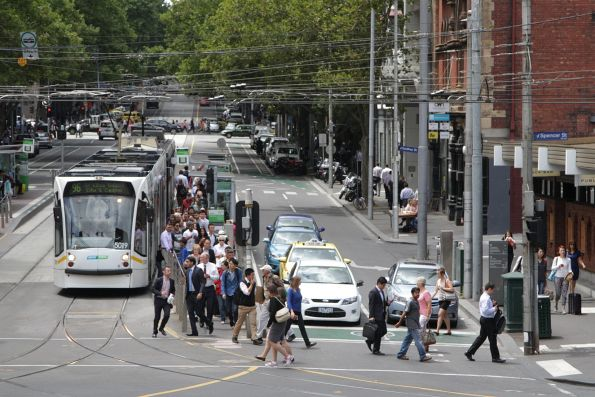 A few more passengers escape the tram stop despite the pedestrian crossing being needlessly red