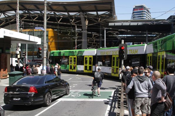 Tram passengers wait to exit the tram stop at the corner of Bourke and Spencer Streets