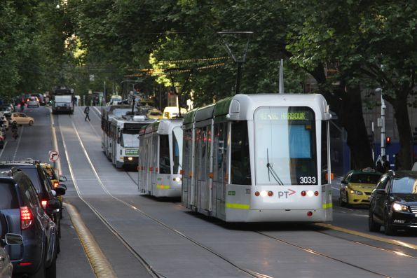 C.3033 on route 48 leads a pack of westbound trams at Collins and King Street