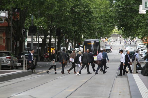 Passengers cross Bourke Street after E2.6057 departs
