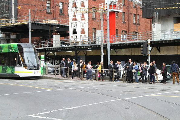 Passengers wait for E.6046 to clear the intersection of Bourke and Spencer Street