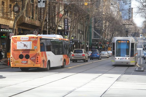 C.3029 on route 48 passes Transdev Melbourne bus #516 2169AO at Collins and Elizabeth Street