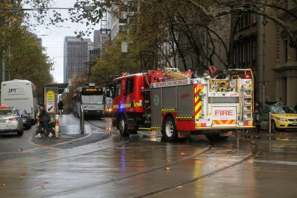 Metropolitan Fire Brigade truck tries to dodge stopped trams at the Collins and Spring Street stop