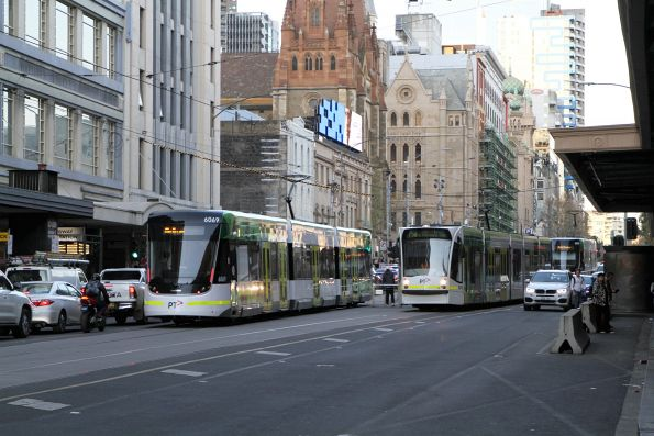 E2.6069 and D2.5016 cross paths on football specials at Flinders and Swanston Street