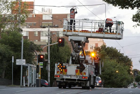 Scissor lift truck deployed on Toorak Road, the crew disconnecting the traction feeder cables to isolate the overhead