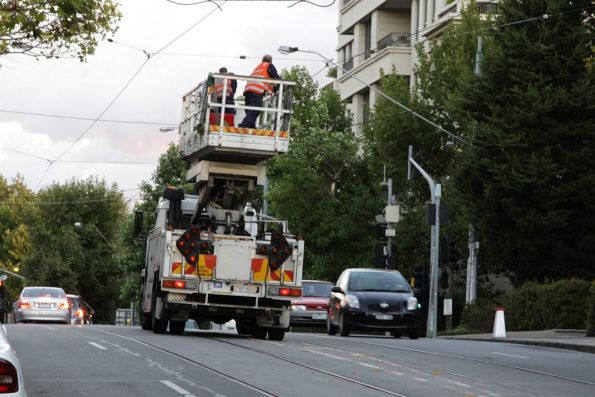 One set of feeder cables isolated from the trolley wire, the crew continue down Toorak Road to disconnect some more