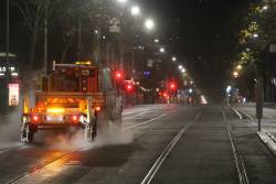 ISS Facility Services ute tows some kind of tram track cleaning equipment along William Street