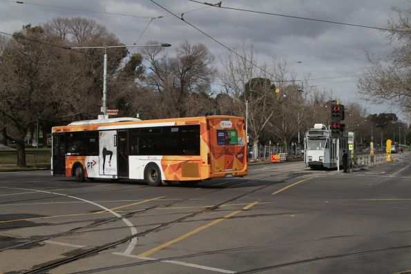 Transdev bus turns into St Kilda Road from Southbank Boulevard, as a northbound tram waits for the traffic lights