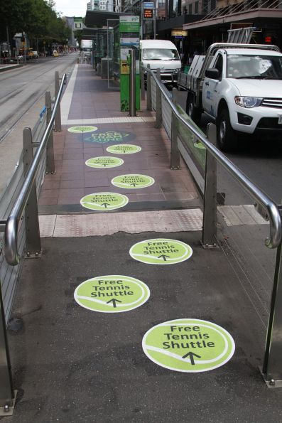 'Free Tennis Shuttle' stickers at the entrance to the Elizabeth Street stop on Flinders Street