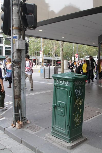 M&MTB branded electrical cabinet at the corner of Collins and Swanston Streets