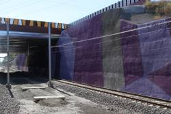 Multicoloured cutting walls at the down end of South Morang station