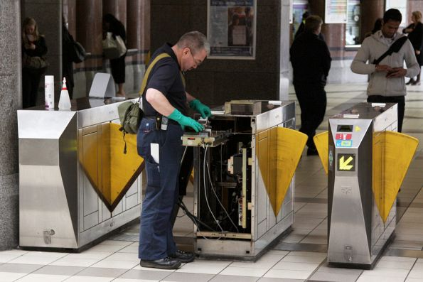 ERG technician cleaning the Metcard slot of a ticket barrier