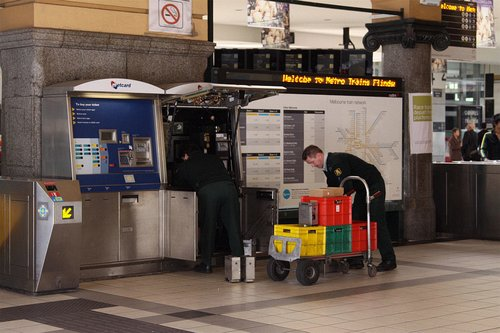 Armaguard staff swapping over the cash vaults from the Metcard machines at Flinders Street Station