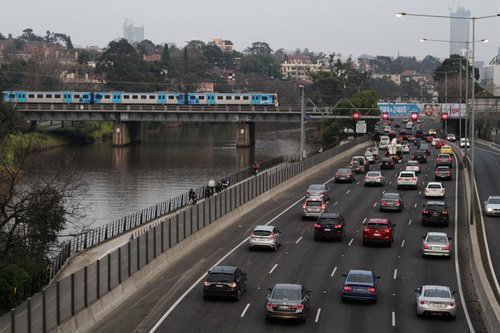 Siemens train crosses the Cremorne railway bridge, with peak hour traffic grinding along the Monash Freeway