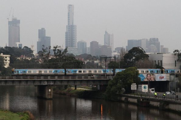 Alstom Comeng crosses the Cremorne railway bridge over the Yarra, with the CBD skyline behind