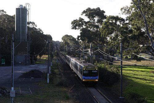 EDI Comeng on a down Cranbourne service passes the disused cement siding at Lyndhurst